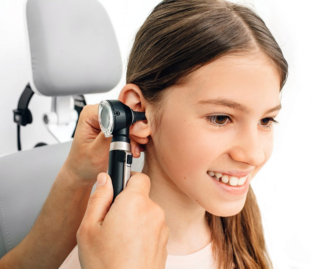 Child hearing exam. Diagnosis of impairment and hearing testing in children. Girl during an ear checkup with an audiologist
